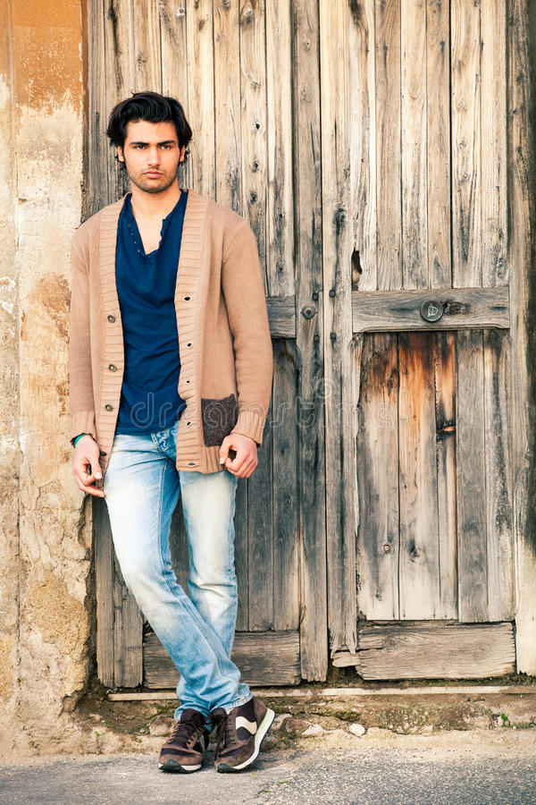 Italian handsome man model near an ancient wooden door royalty free stock photo