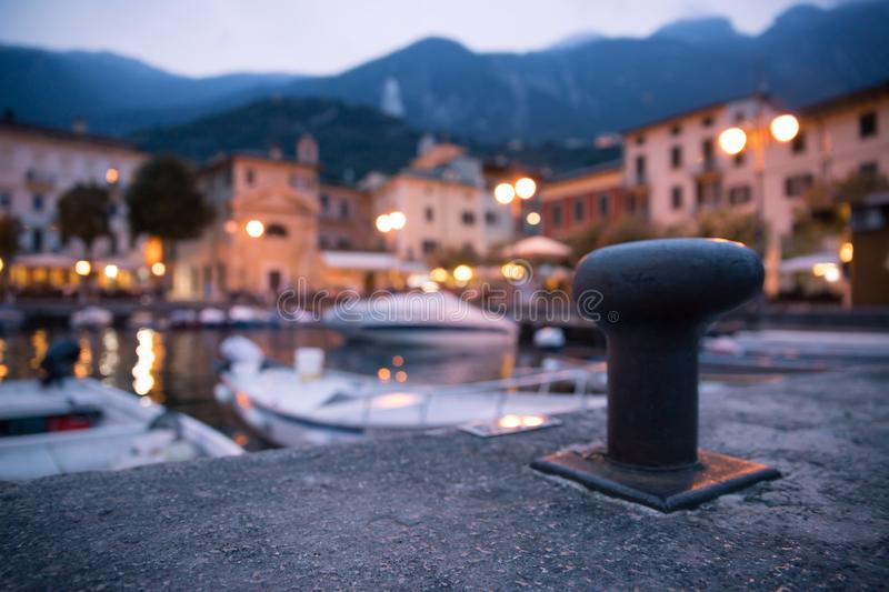 Italian harbour scene on the evening: cute village in the blurry background. Italian harbour in the evening, small cute village and lighrs in the blurry royalty free stock images