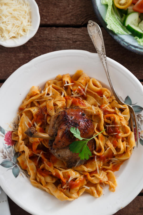 Italian homemade pasta, pappardelle with tomato sauce and braised rabbit, top view close-up.  royalty free stock image