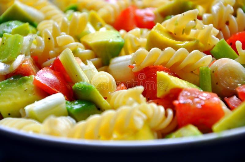 Italian iconic food : pasta. Vegan dish with italian pasta with fresh tomatoes , avocado and onion. italian typical food concept stock image