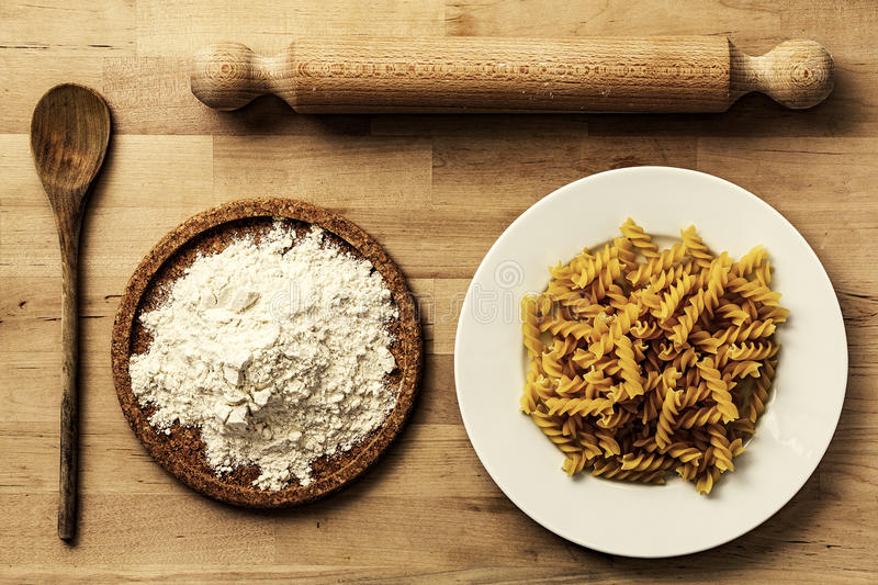 Italian ingredients homemade. Raw pasta, flour, rolling pin, wooden spoon on rustic surface royalty free stock photography