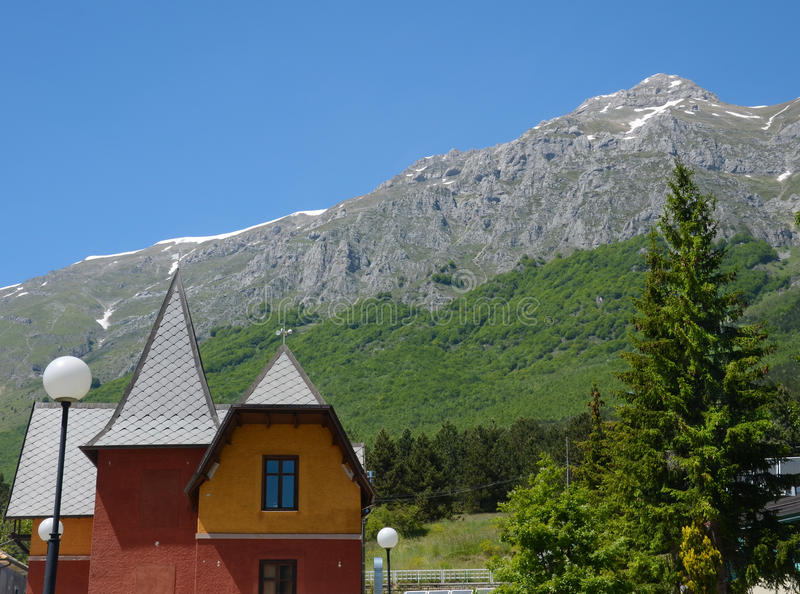 Italian landscape in summer - snowy mountain and house royalty free stock images
