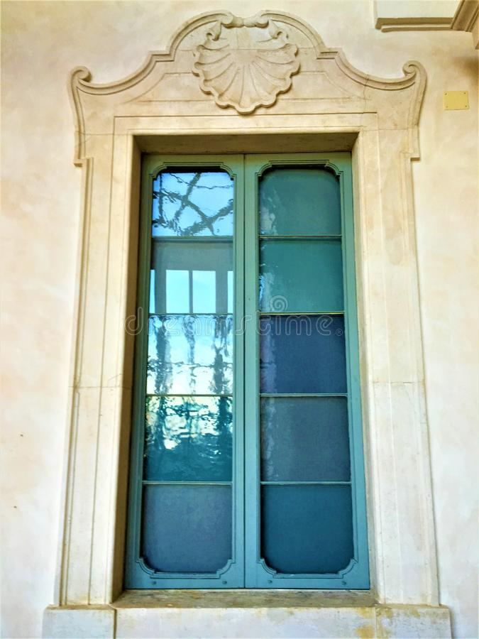 Liberty style window, azure glass and shell. Italian Liberty style window, azure glass, artistic shell, reflection and mirror, vintage wall and building, shades stock photos