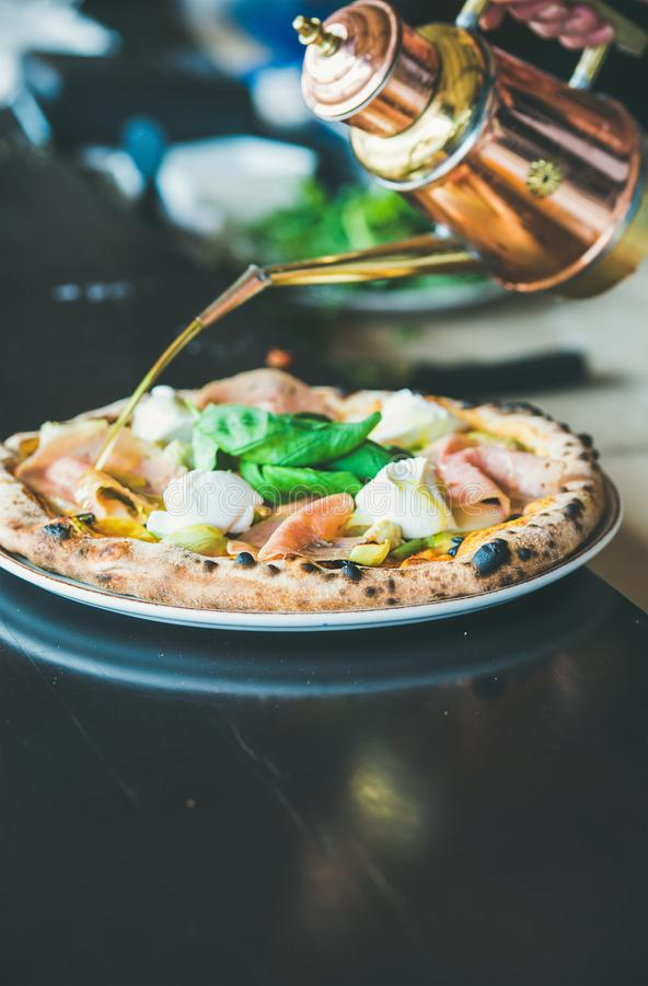 Freshly baked Italian pizza with ham, artichokes served in restaurant stock photo