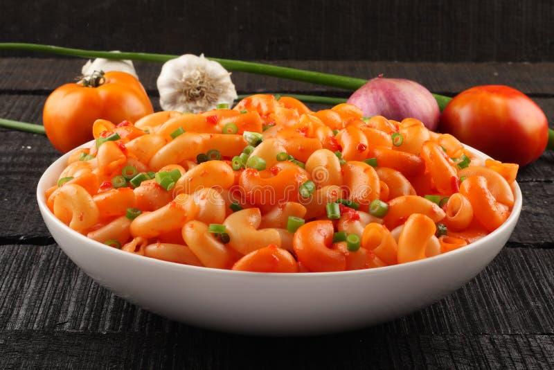 Italian macaroni pasta in tomato sauce and herbs, royalty free stock photo
