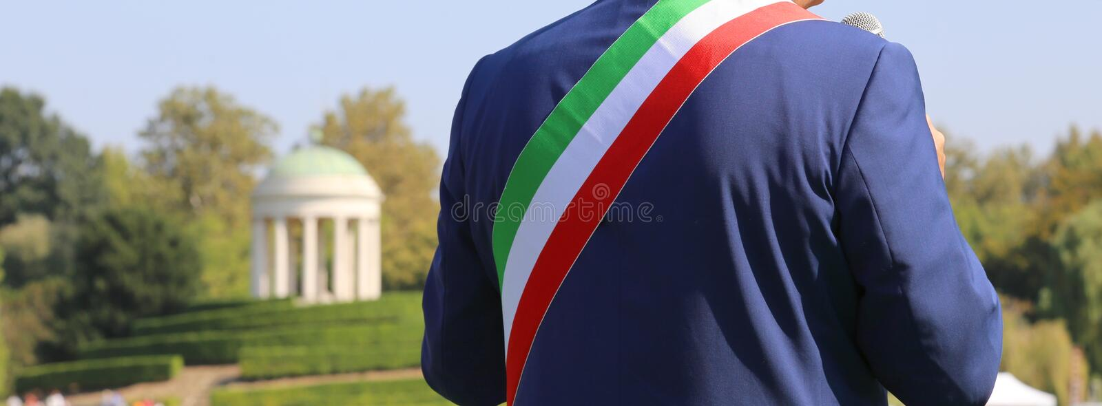 Italian mayor with the tricolor flag at a public event outdoors. Italian mayor with the tricolor flag and the small temple in the background at a public event stock photography