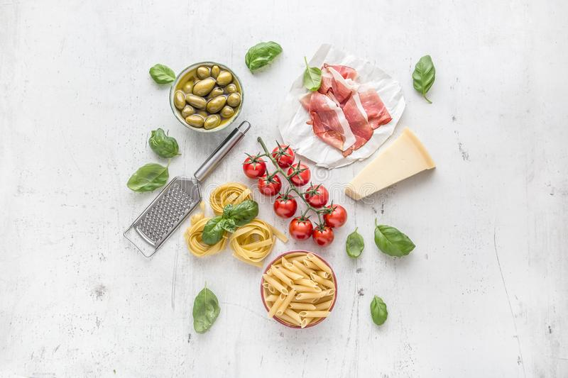 Italian or mediterranean food cuisine and ingredients on white concrete table. Tagliatelle pene pasta olives olive oil tomatoes royalty free stock photography
