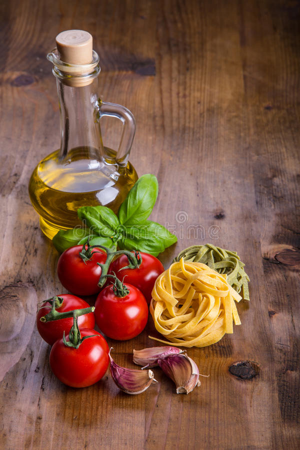 Italian and Mediterranean food ingredients on wooden background.Cherry tomatoes pasta, basil leaves and carafe with olive oil. Italian and Mediterranean food royalty free stock photography