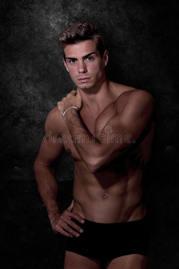 Italian model muscular man. Underwear portrait. Italian model muscular man. Black underwear portrait. A young Italian boy shirtless posing on a grunge black and stock image