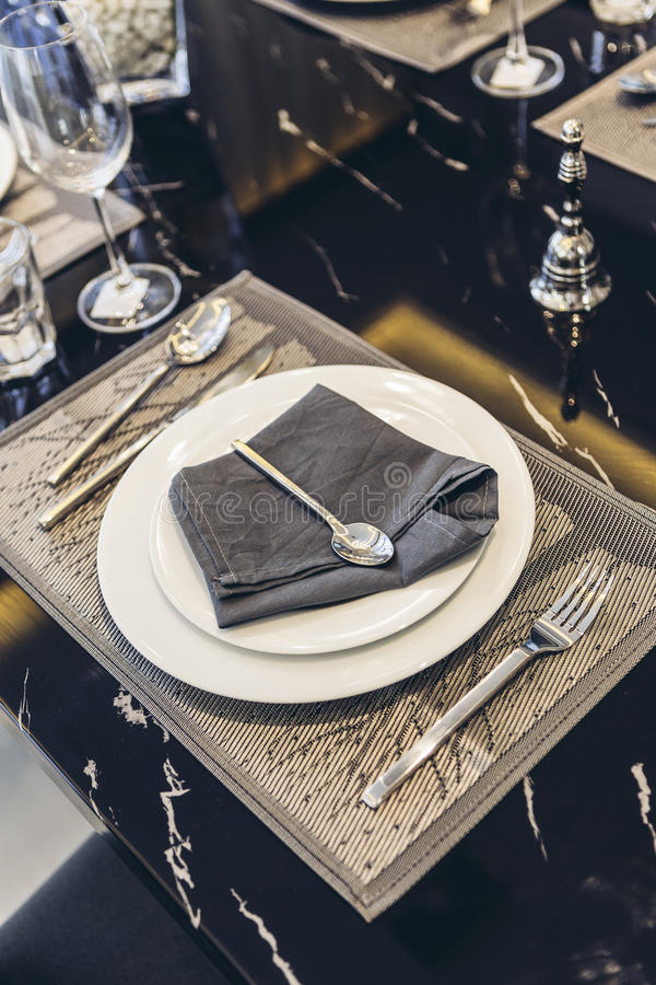 Italian Modern Model House : White Plate and Blue Napkin with Silver Spoon and Fork Dinning Set royalty free stock image