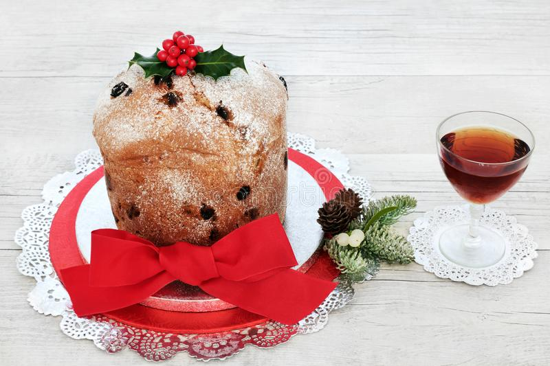 Italian Panettone Christmas Cake. And alcoholic drink with winter flora of holly, fir and mistletoe on rustic wood table background. Traditional sweet bread royalty free stock photos