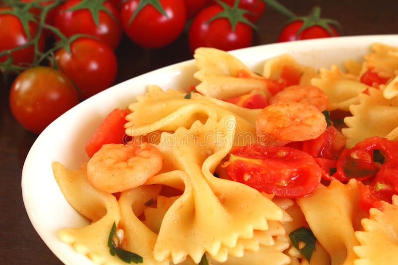 Italian pasta. A dish of italian pasta with shrimps and tomatoes with a bunch of cherry tomatoes at the background stock photography
