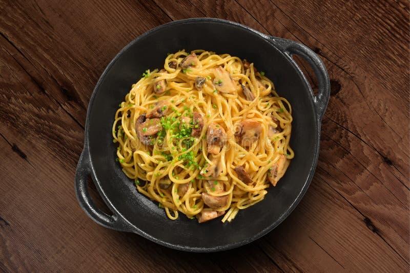 Traditional Italian pasta on black rustic pan stock photography