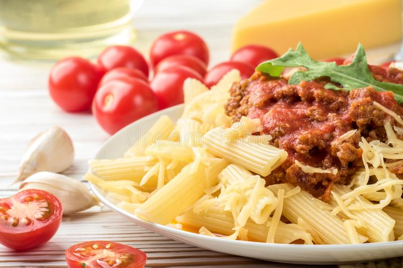 Italian pasta bolognese penne rigatone minced meat in tomato sauce and parmesan cheese. Still life on white wooden table served stock image