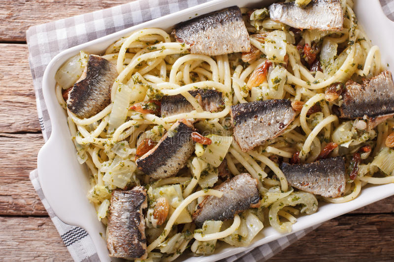 Italian pasta bucatini with sardines, fennel, raisins and pine n. Uts close up in baking dish. horizontal view from above stock image