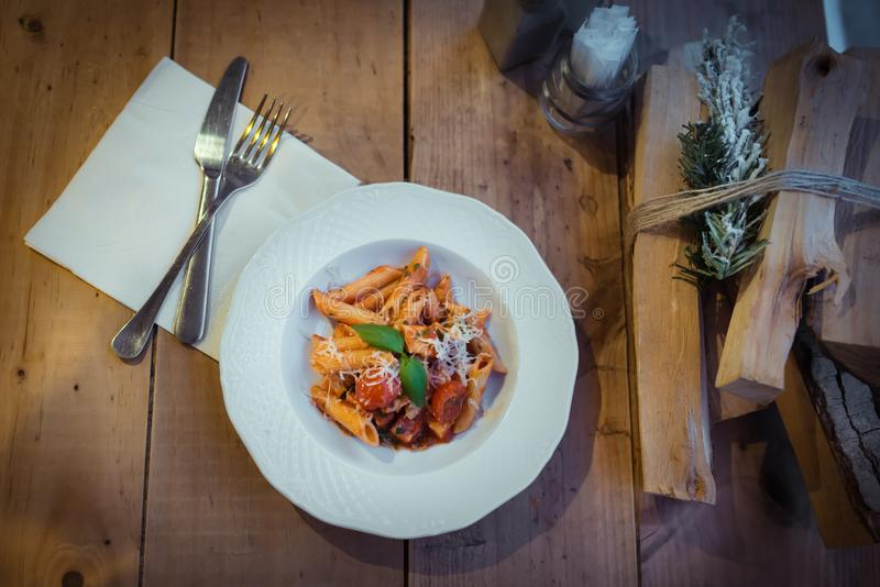 Italian pasta on Christmas dinner. On the wooden table. Bundle of firewood also here. Blue color, orange color stock photo