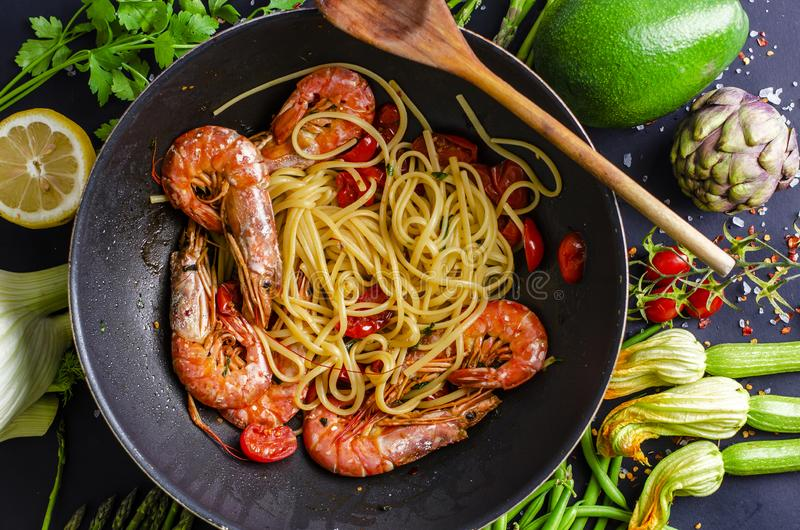 Italian pasta cooking with tiger prawns or shrimps royalty free stock photos