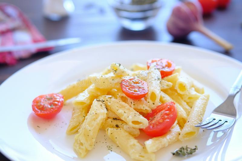 Italian pasta with cream sauce, cheese, sour cream, tomatoes and spices on a white plate on a wooden table. Lying next to a fork. royalty free stock images