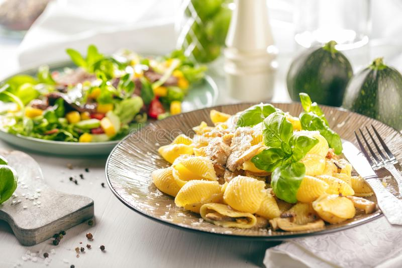 Italian pasta in a creamy sauce with salad on a plate, close-up. royalty free stock photo