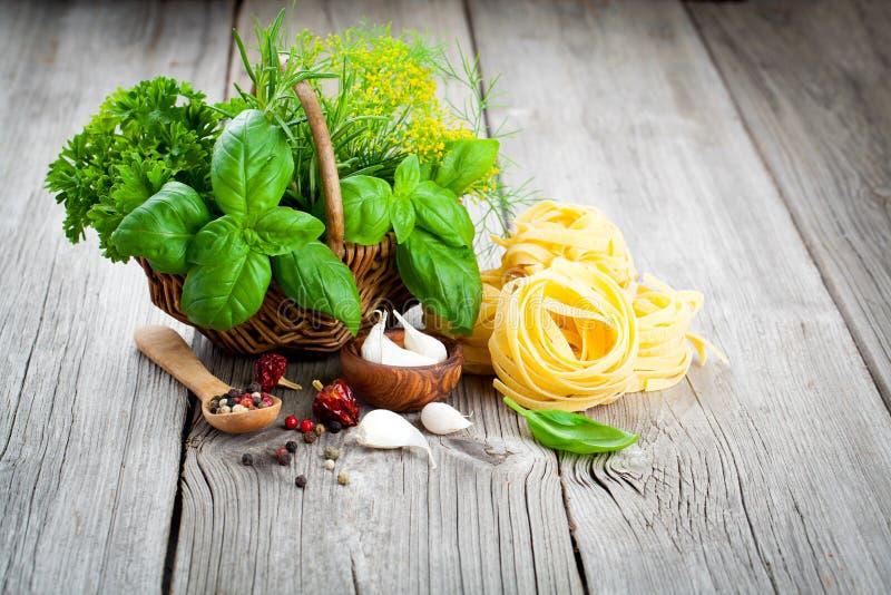 Italian pasta fettuccine nest with wicker basket green herbs. On wooden background stock image