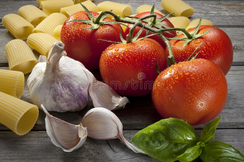 Italian Pasta Food Ingredients. Classic Italian food ingredients for making a meal with tomatoes, basil, garlic and pasta on a wood background royalty free stock photography