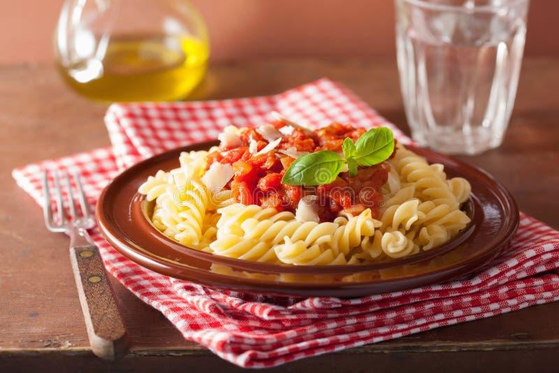 Italian pasta fusilli with tomato sauce and basil royalty free stock photography
