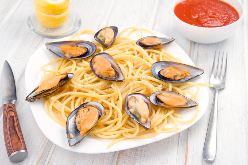 Italian pasta with Galician mussels in wood. Italian pasta with Galician mussels in white wood stock photography