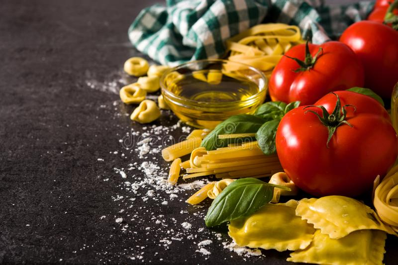 Italian pasta and ingredients. Ravioli, penne pasta, spaghetti, tortellini, tomatoes and basil on black background. royalty free stock image