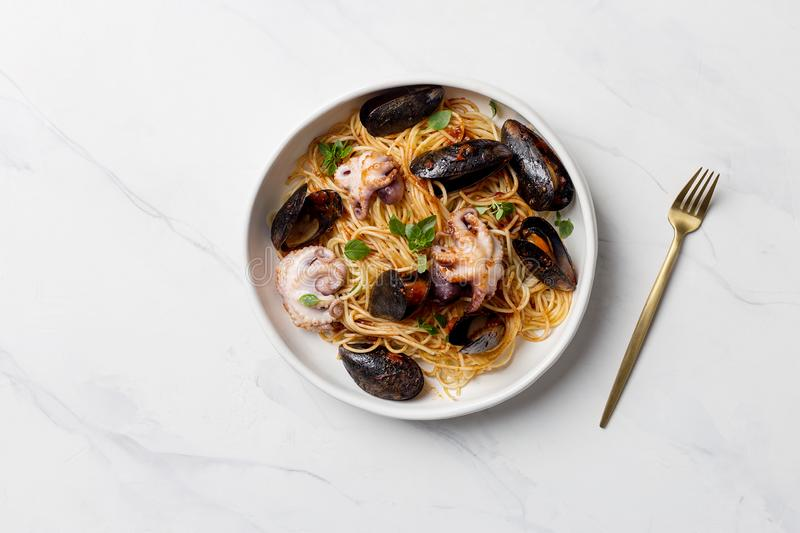 Italian pasta with mussels and octopus in white plate. With golden fork on white marble background. Concept of Italian dinner stock photography