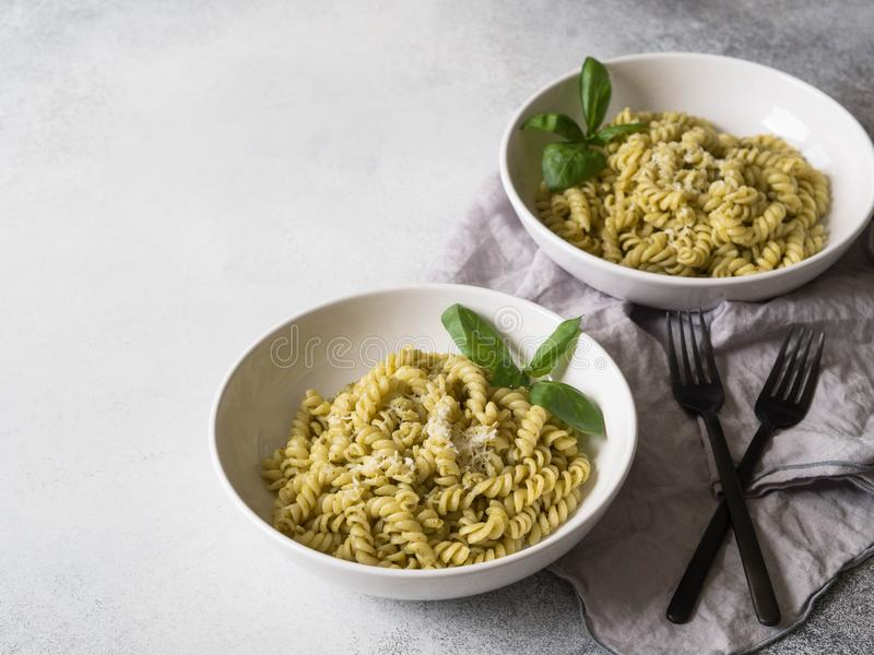 Italian pasta with pesto sauce, fresh basil and Parmesan in a white bowls on grey background. Cope space stock photo