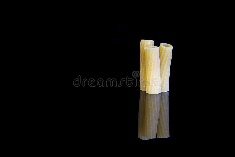 Rigatoni raw italian pasta isolated on black background royalty free stock photography