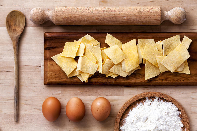 Italian pasta. Rolling pin, flour, eggs, ladle. Wooden surface. stock photo