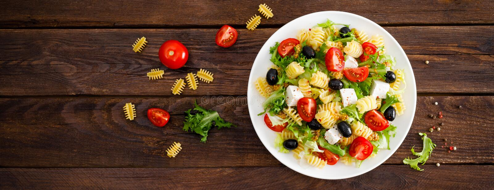 Italian pasta salad with fresh tomato, cheese, lettuce and olives on wooden background. Mediterranean cuisine. Banner. Italian pasta salad with fresh tomato stock photos