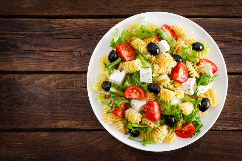 Italian pasta salad with fresh tomato, cheese, lettuce and olives on wooden background. Mediterranean cuisine. Cooking lunch. Hea royalty free stock image