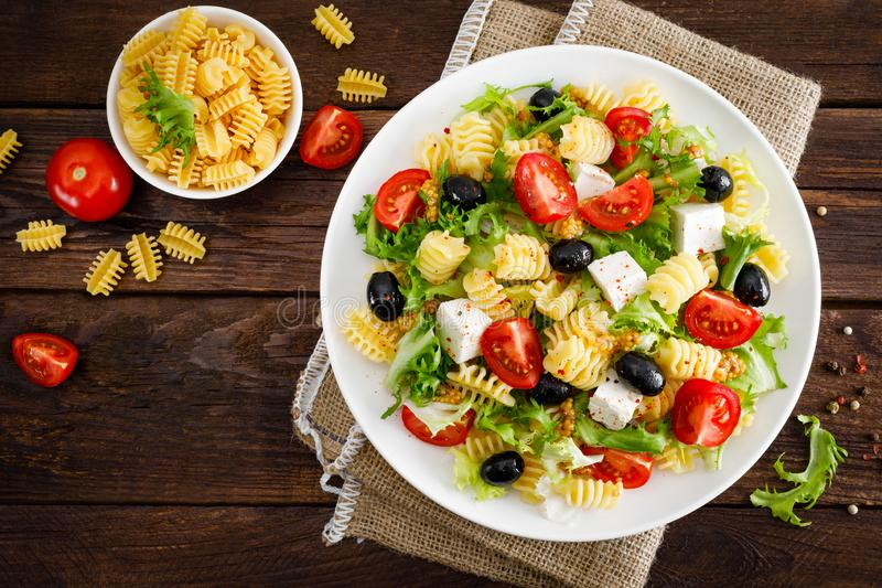 Italian pasta salad with fresh tomato, cheese, lettuce and olives on wooden background. Mediterranean cuisine. Cooking lunch. Hea. Lthy diet food. Top view royalty free stock photography