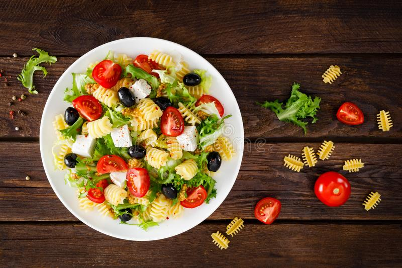 Italian pasta salad with fresh tomato, cheese, lettuce and olives on wooden background. Mediterranean cuisine. Cooking lunch. Hea. Lthy diet food. Top view stock photography