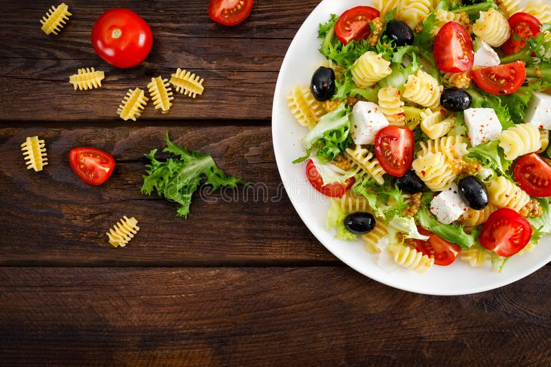 Italian pasta salad with fresh tomato, cheese, lettuce and olives on wooden background. Mediterranean cuisine. Cooking lunch. Hea. Lthy diet food. Top view stock photo