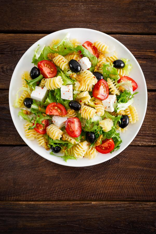 Italian pasta salad with fresh tomato, cheese, lettuce and olives on wooden background. Mediterranean cuisine. Cooking lunch. Healthy diet food. Top view stock image