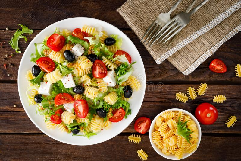 Italian pasta salad with fresh tomato, cheese, lettuce and olives on wooden background. Mediterranean cuisine. Cooking lunch. Hea. Lthy diet food. Top view royalty free stock image
