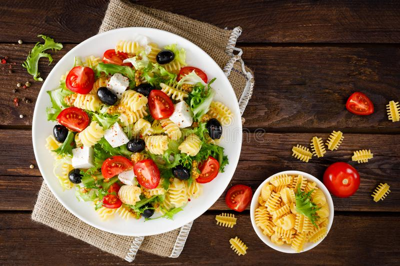 Italian pasta salad with fresh tomato, cheese, lettuce and olives on wooden background. Mediterranean cuisine. Cooking lunch. Hea. Lthy diet food. Top view royalty free stock images