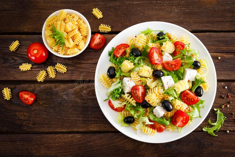 Italian pasta salad with fresh tomato, cheese, lettuce and olives on wooden background. Mediterranean cuisine. Cooking lunch. Hea. Lthy diet food. Top view royalty free stock photo