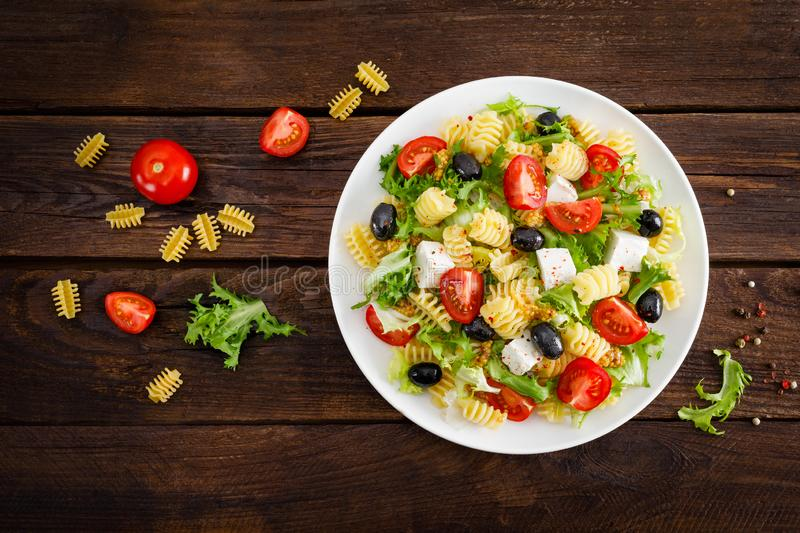 Italian pasta salad with fresh tomato, cheese, lettuce and olives on wooden background. Mediterranean cuisine. Cooking lunch. Hea. Lthy diet food. Top view stock image