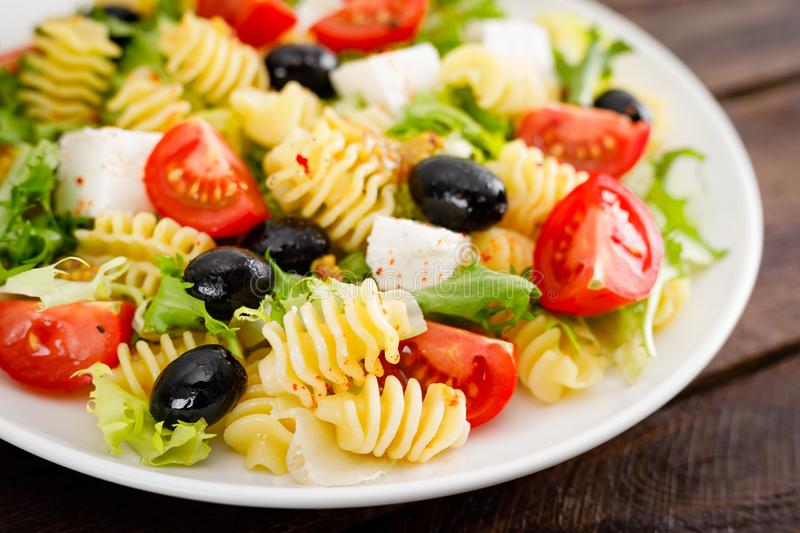 Italian pasta salad with fresh tomato, cheese, lettuce and olives on wooden background. Mediterranean cuisine. Cooking lunch. Healthy diet food royalty free stock image