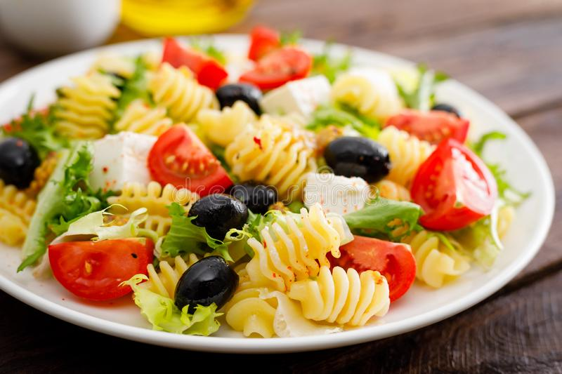 Italian pasta salad with fresh tomato, cheese, lettuce and olives on wooden background. Mediterranean cuisine. Cooking lunch. Healthy diet food royalty free stock photos