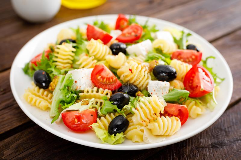 Italian pasta salad with fresh tomato, cheese, lettuce and olives on wooden background. Mediterranean cuisine. Cooking lunch. Healthy diet food royalty free stock photography