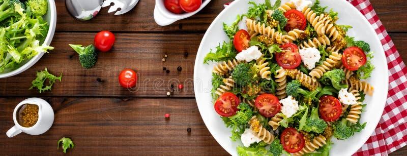 Italian pasta salad with wholegrain fusilli, fresh tomato, cheese, lettuce and broccoli on wooden rustic background. Banner. Italian pasta salad with wholegrain stock images
