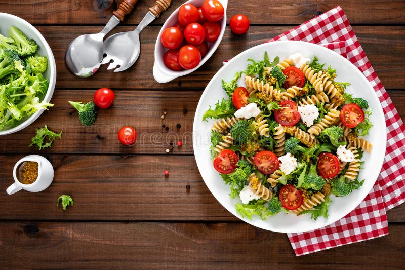 Italian pasta salad with wholegrain fusilli, fresh tomato, cheese, lettuce and broccoli on wooden rustic background. Mediterranean cuisine. Cooking lunch royalty free stock image