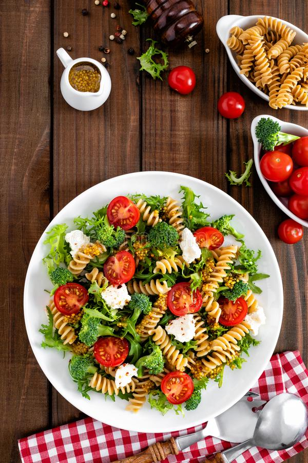 Italian pasta salad with wholegrain fusilli, fresh tomato, cheese, lettuce and broccoli on wooden rustic background. Mediterranean cuisine. Cooking lunch stock image