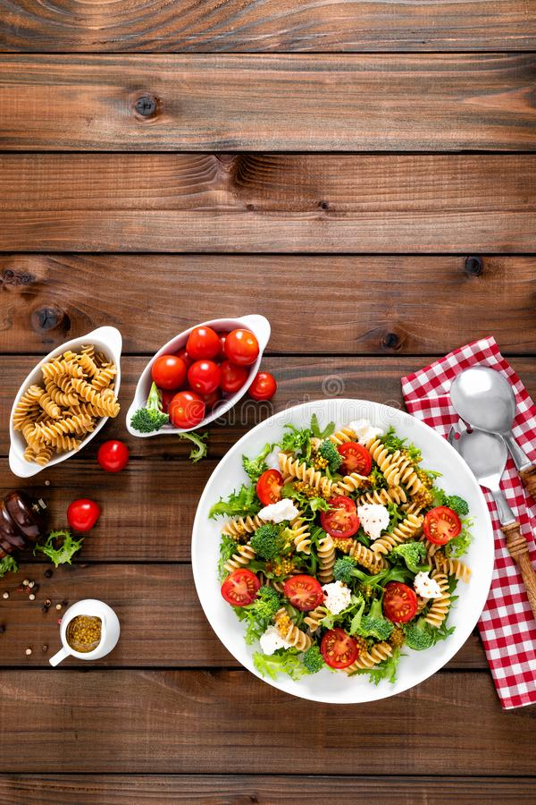 Italian pasta salad with wholegrain fusilli, fresh tomato, cheese, lettuce and broccoli on wooden rustic background. Mediterranean cuisine. Cooking lunch stock photo