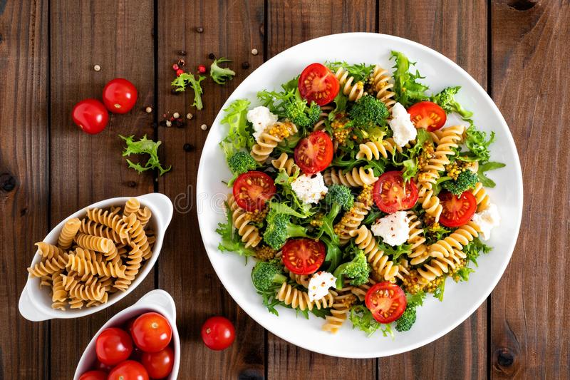 Italian pasta salad with wholegrain fusilli, fresh tomato, cheese, lettuce and broccoli on wooden rustic background. Mediterranean cuisine. Cooking lunch royalty free stock photo